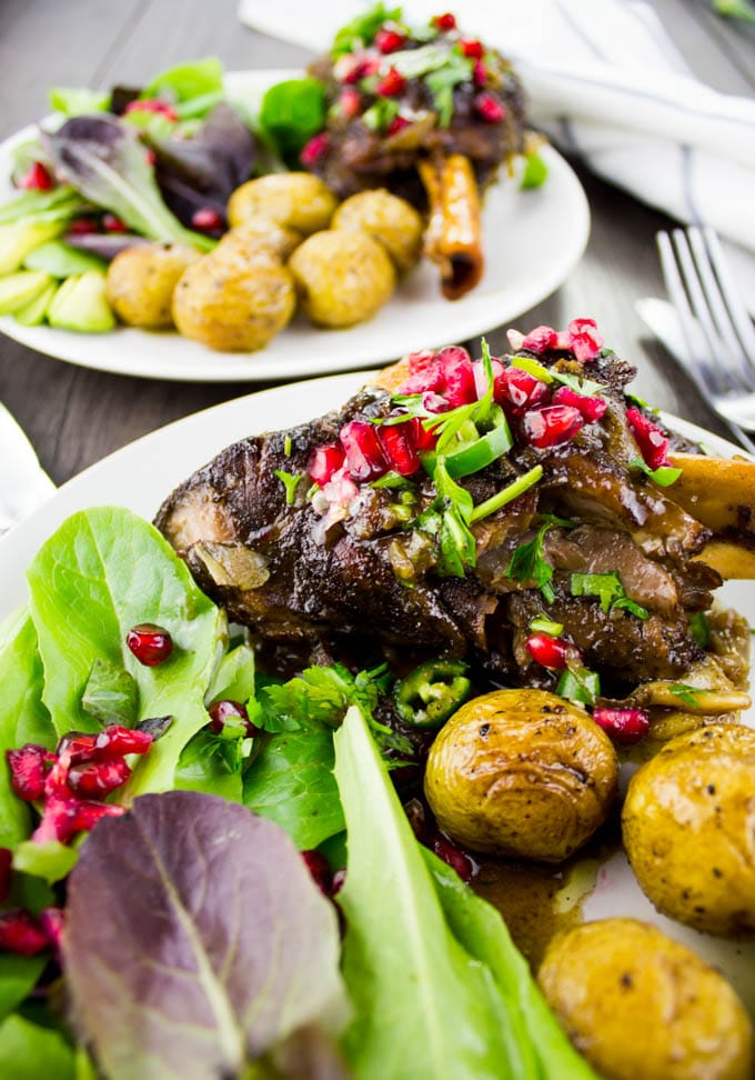close-up of a plate of Pomegranate Roasted Lamb Shanks with potatoes and a salad