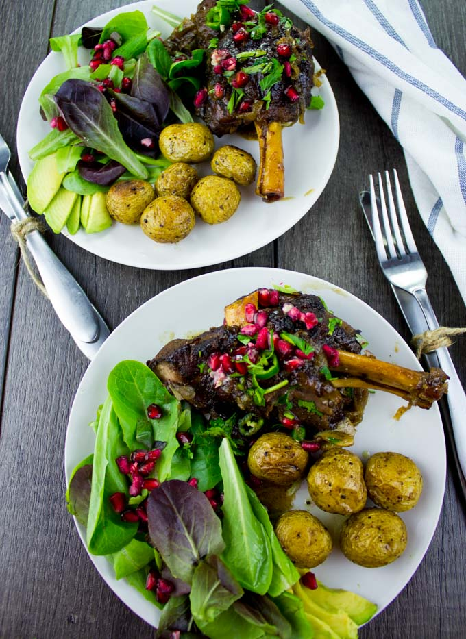 overhead shot of two plates of Pomegranate Roast Lamb Shanks with potatoes and a side salad