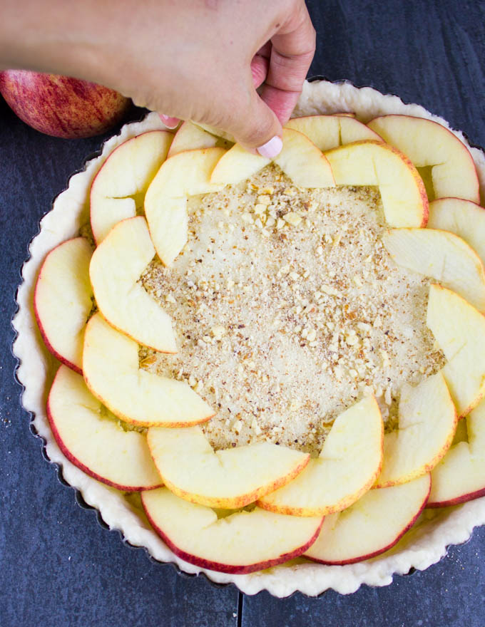apple slices being arranged on top of a layer of almonds to make Swiss Apple Tart