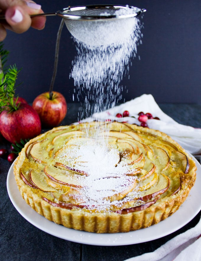 Swiss Apple Tart being dusted with icing sugar