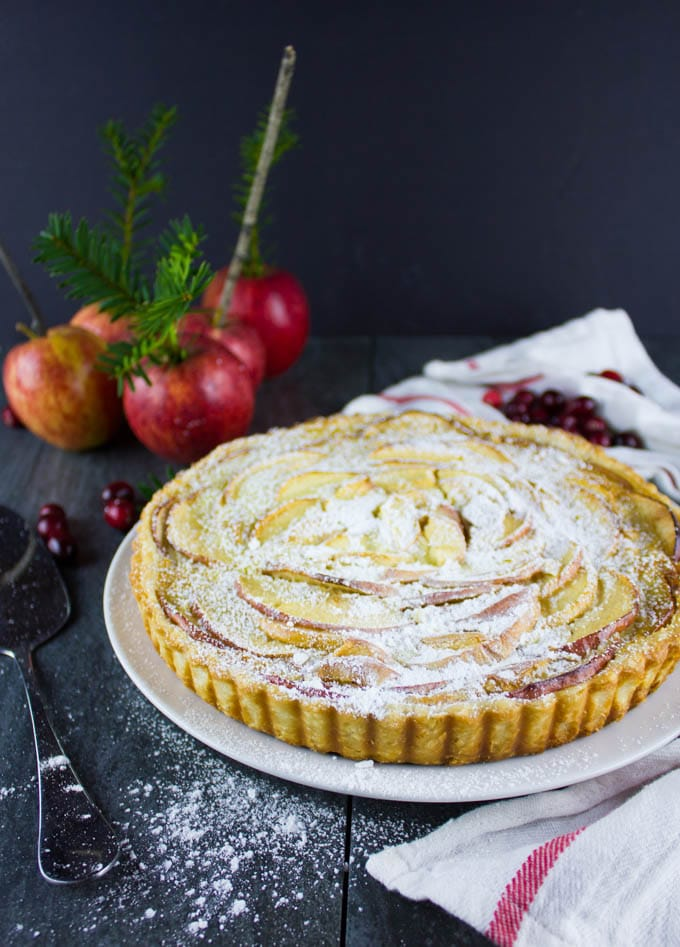Swiss Apple Tart on a rustic wooden table with apples and spruce twigs in the background
