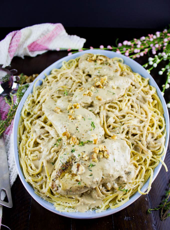 close-up of a bowl of Creamy Walnut Chicken over spaghetti in a blue bowl