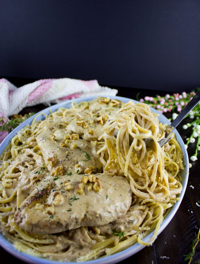 Creamy Walnut Chicken served over pasta in a big blue bowl