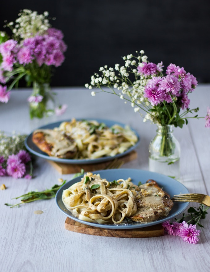 two plates of winner winner chicken dinner with pan seraed chicken breasts and wlanut sauce over pasta. Some pink flowers surrounding the plates