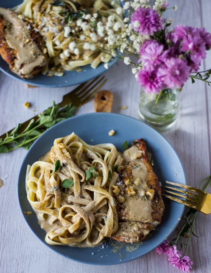 A single plate of the chicken dinner showing the pasta on one side drenched in walnut sauce and the chicken on the other side. A fork is shown on the side of the plate and a small vase of flowers.
