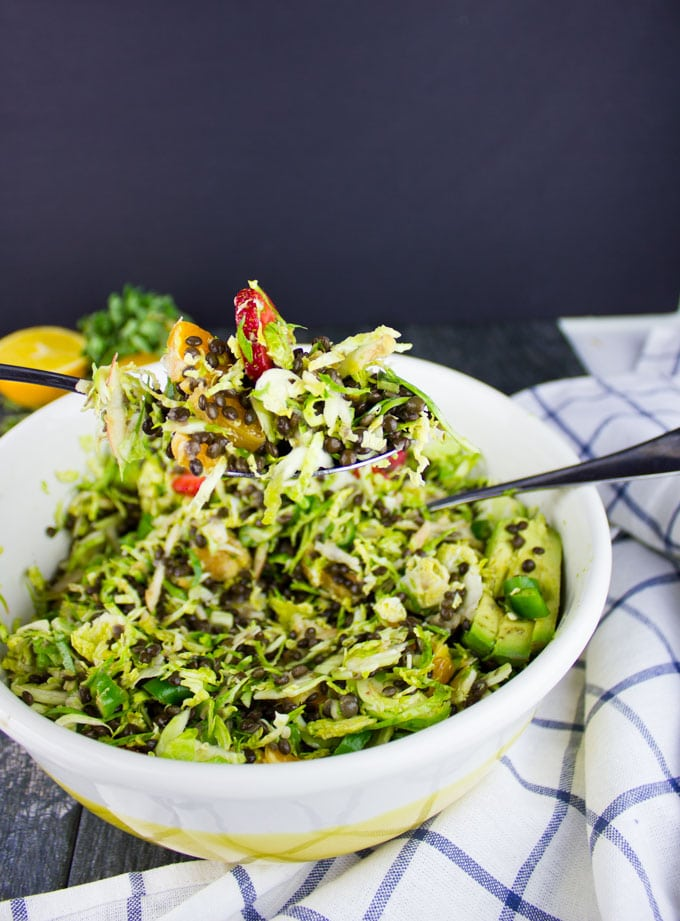 Citrus Lentil Salad with Shredded Brussel Sprouts being tossed in a salad bowl