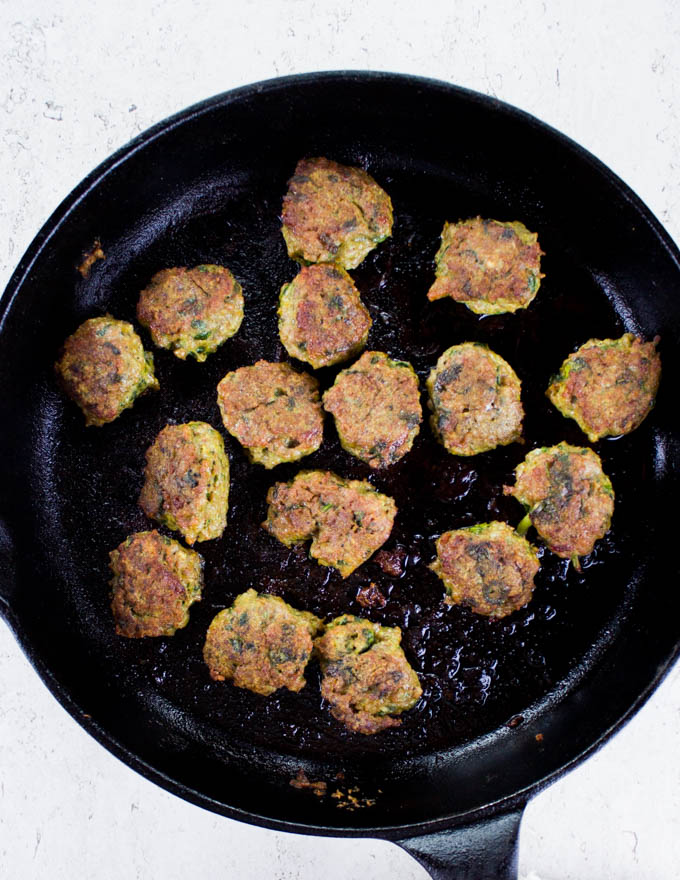 Thai Chicken Meatballs frying in a black skillet