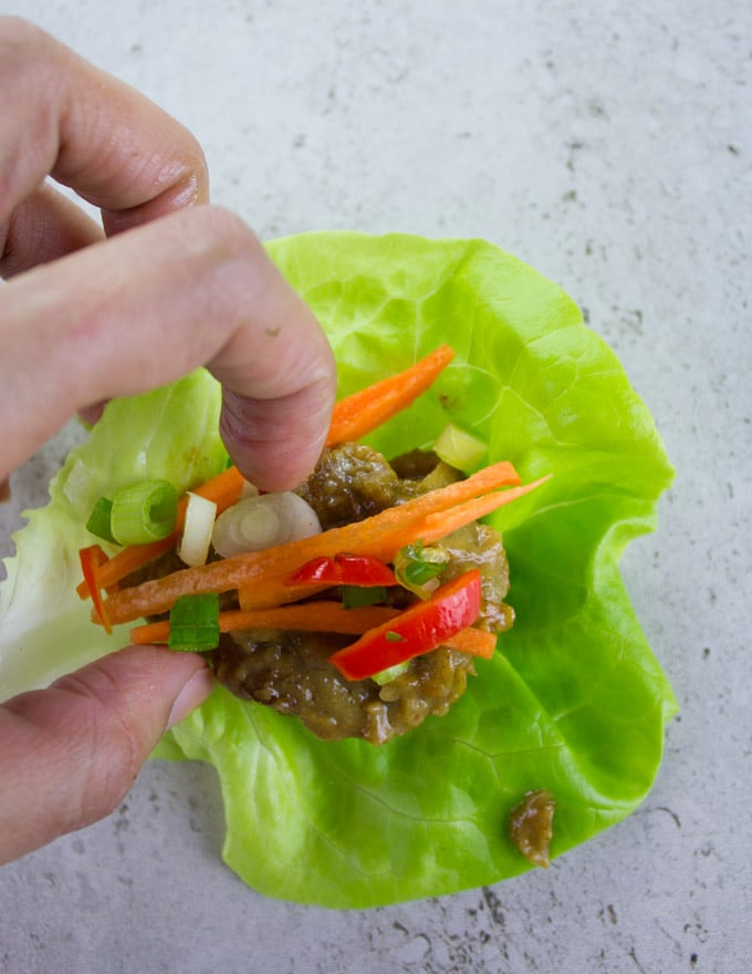 a Thai chicken meatball lettuce wrap being assembled