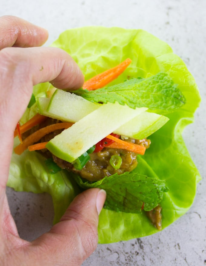shredded apples being added to a chicken meatball lettuce wrap