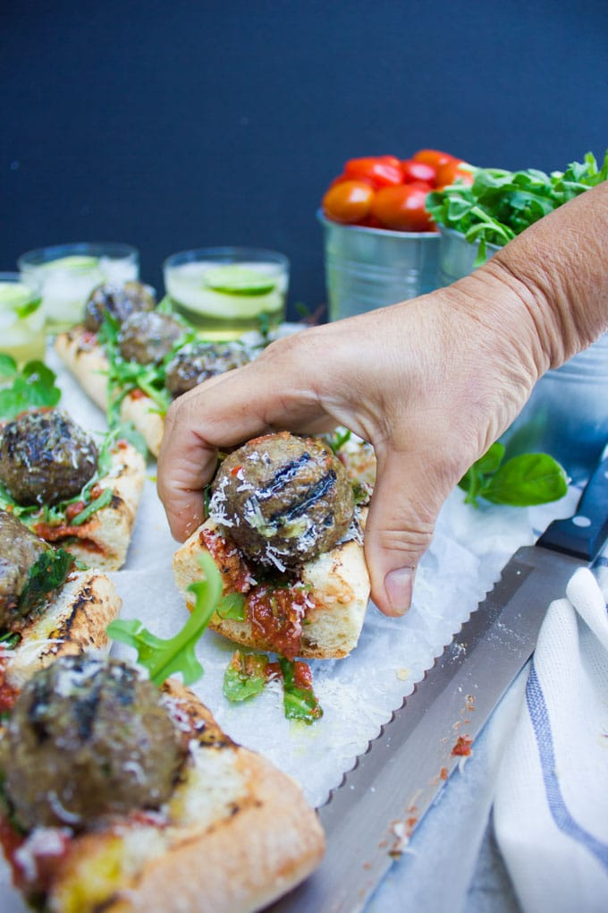 a hand reaching for a piece of Grilled American Lamb Meatball Sub