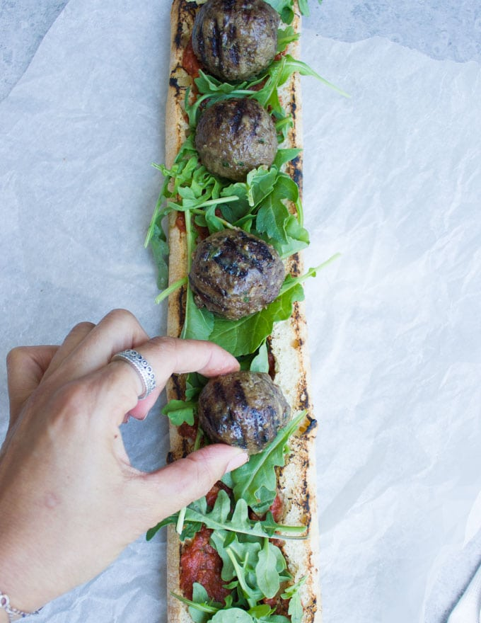 grilled lamb meatballs being lined up on top of open-faced sandwich