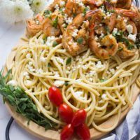 Quick Shrimp Pasta with Garlic Feta Sauce on a wooden platter