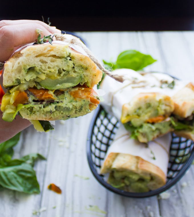 a hand holding half a Roasted Veggie Sandwich with Basil Sauce held together with parchment paper and string