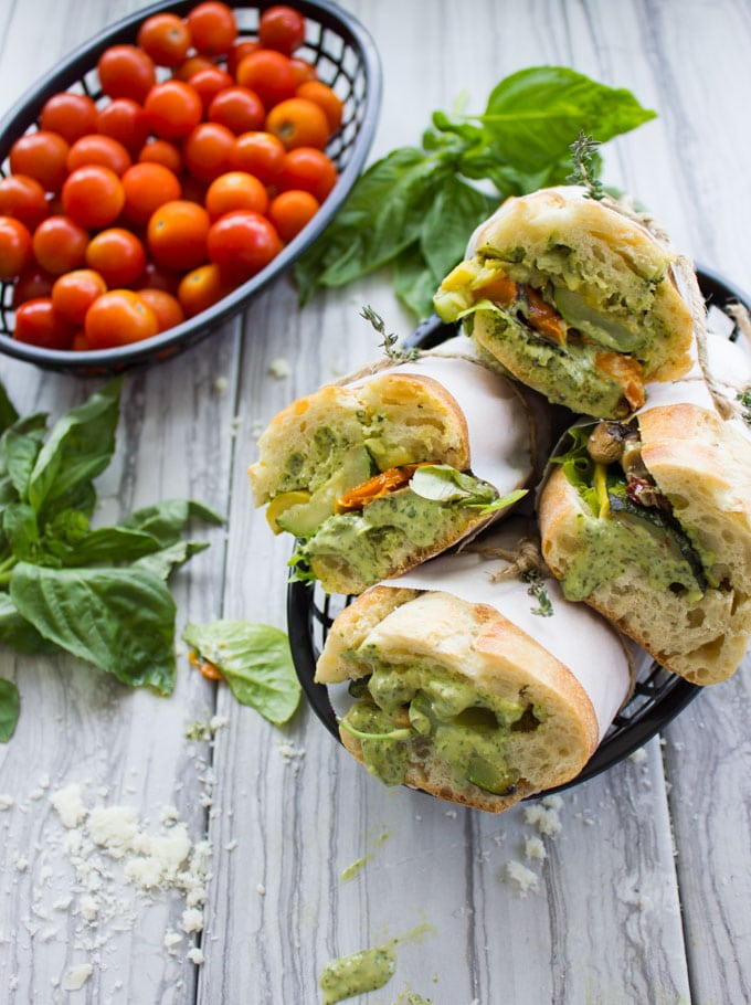 four Roast Veggie Sandwiches with Basil Sauce in a black basket with fresh basil on the side
