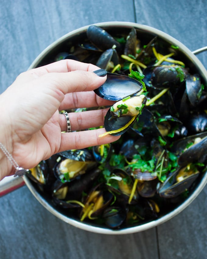 A hand showing a cooked mussel out of its' shell ready to be eaten right away over a skillet of cooked mussels.