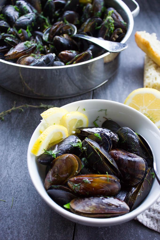One bowl with lemon slices and mussels cooked.