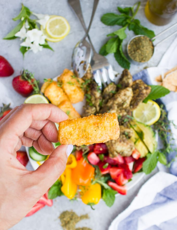 a hand holding a fried halloumi cheese stick over a bowl of za'atar chicken salad