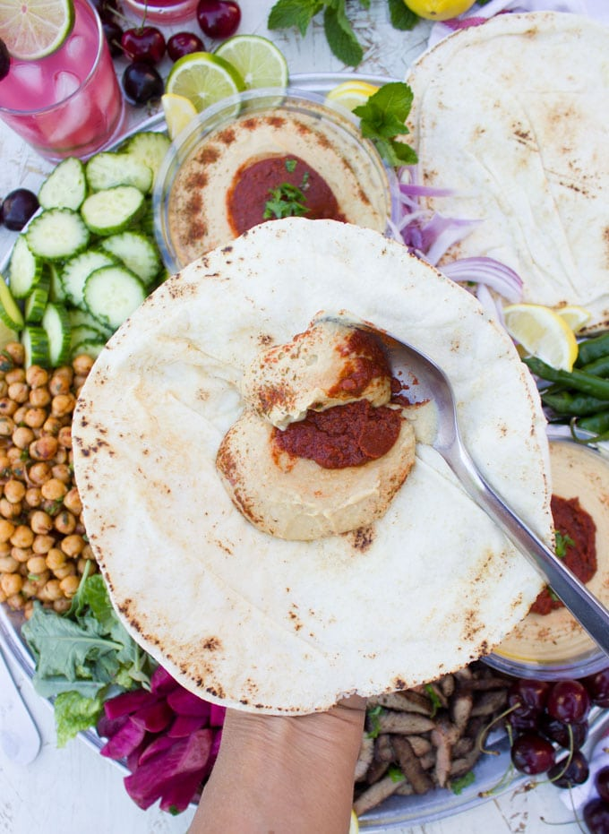 spreading the hummus on a pita bread