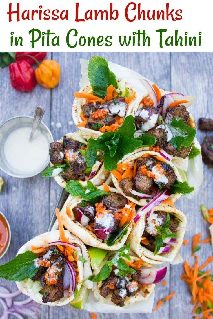 This simple yet flavor loaded recipe for Spicy Harissa Lamb Shoulder Chunks in Pita Cones with Tahini Sauce will blow you away! A blend of cubed lamb shoulder seared with plenty of garlic and olive oil until charred and tender then seasoned with a fresh pepper Harissa sauce and piled into homemade pita cones.#pitacones, #lambrecipes, #middleeasternrecipes, #partyfood