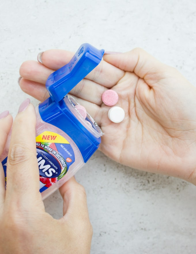 An opened TUMS bottle with tablets poured in to a hand