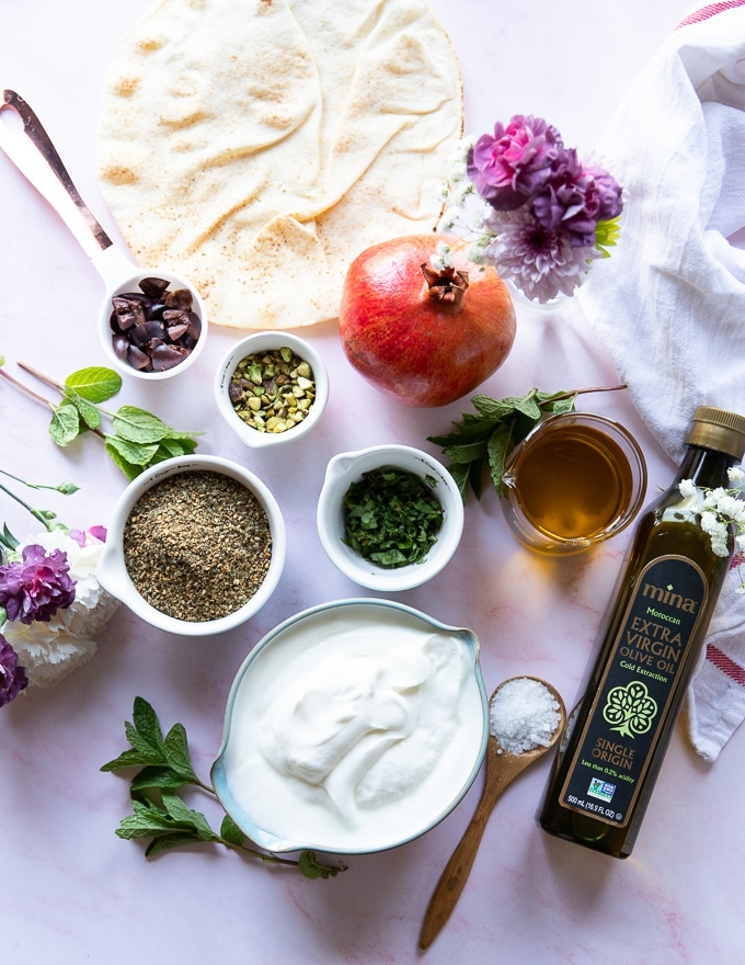 Ingredients to make labneh with a zaatar topping using moroccan olive oil, zaatar, pistachio, mint, and pomegranate