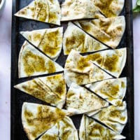 pita bread cut into wedges over a baking tray, brushed with zaatar olive oil and ready to bake for chips