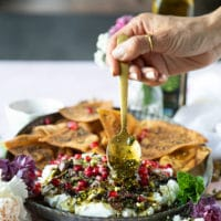 A hand spooning over the toppings over the spread out labneh over a serving plate with the pita chips