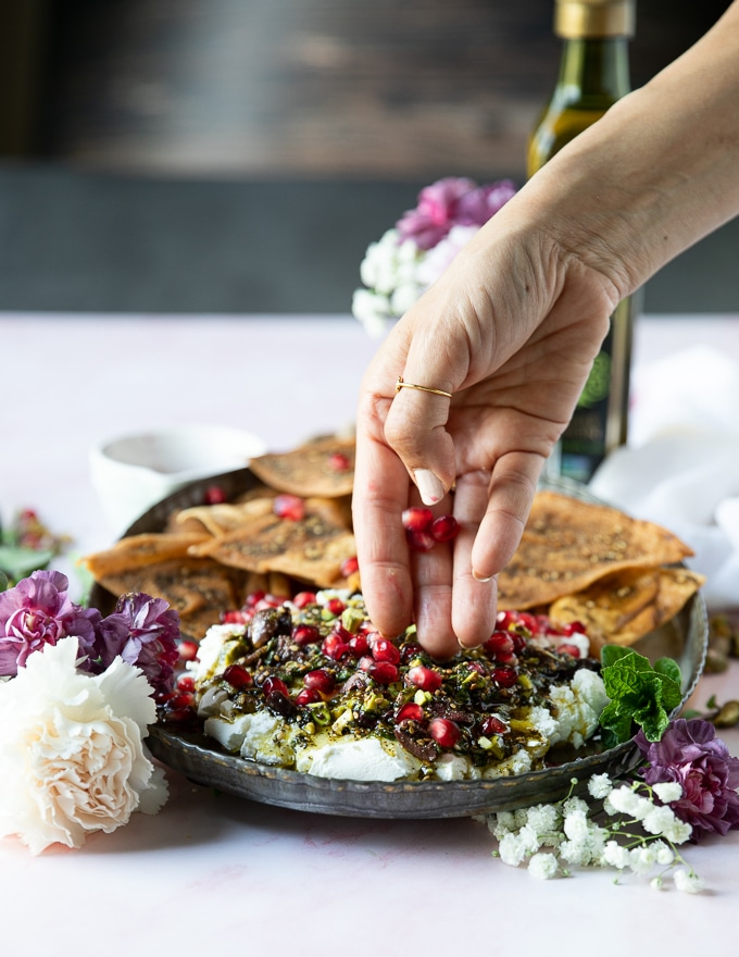 A hand sprinkling some pomegranate seeds