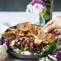 A plate of labneh dip topped with zaatar and a hand holding pita chips dipping it in the dip