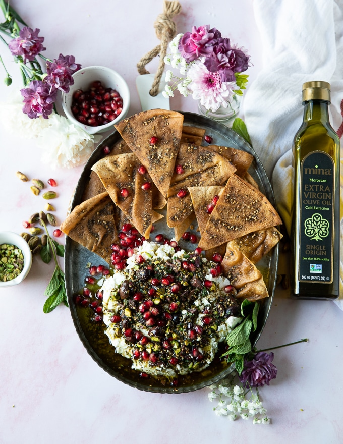 A top view of a full labneh dip platter with zaatar pita chips