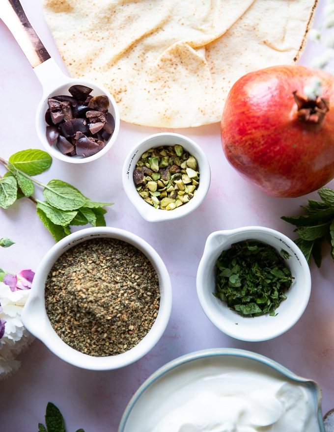 toppings for labneh dip including zaatar, olives, mint, pomegranates, pistachios and olive oil