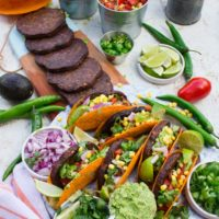 A tacos party set up with grilled burgers, assembled tacos, guacamole, salsa and fresh cilantro toppings