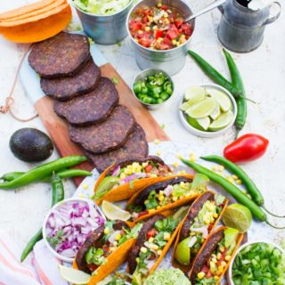 Top view of A burger taco party with all the ingredients taco shells, grilled burgers, guacamole, salsa, chopped jalapenos and chopped onions