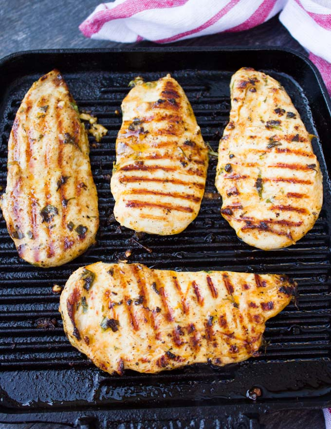 grilled chicken breasts on a grill skillet ready to eat