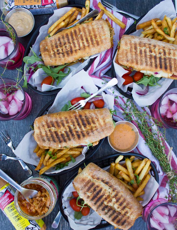 A top view table set up with four panini pressed sandwiches served with fries and some drinks on the side