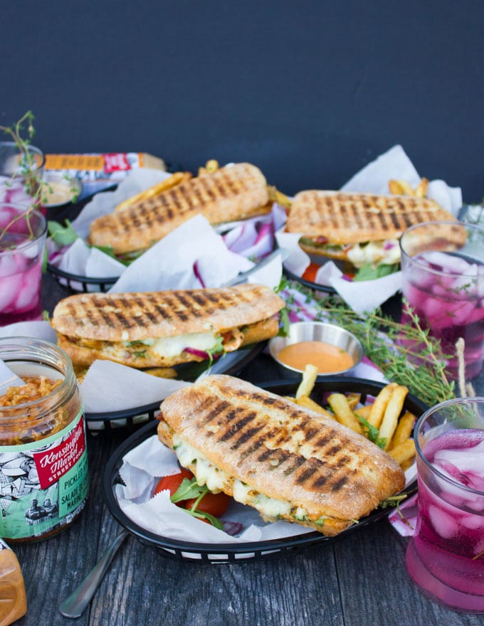 a side view showing a table set up with four panini pressed sandwiches served with fries and some drinks on the side