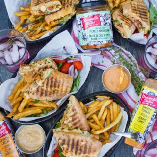 a top view table spread showing four plates with four sandwiches split in half served with some fries and cold drinks