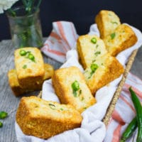 A basket with a few cornbread muffins and some spicy green chillies and a kitchen towel