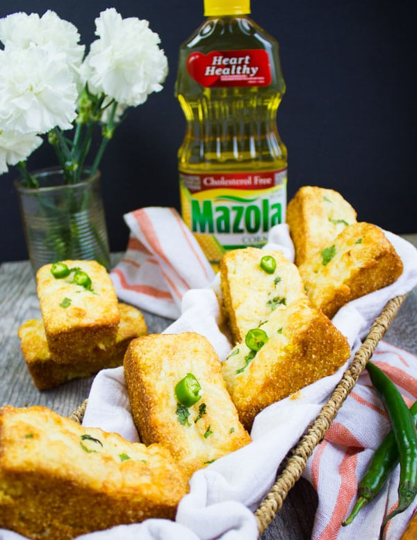 A huge basket with cornbread muffins and a bottle of mazola oil and a kitchen towel around