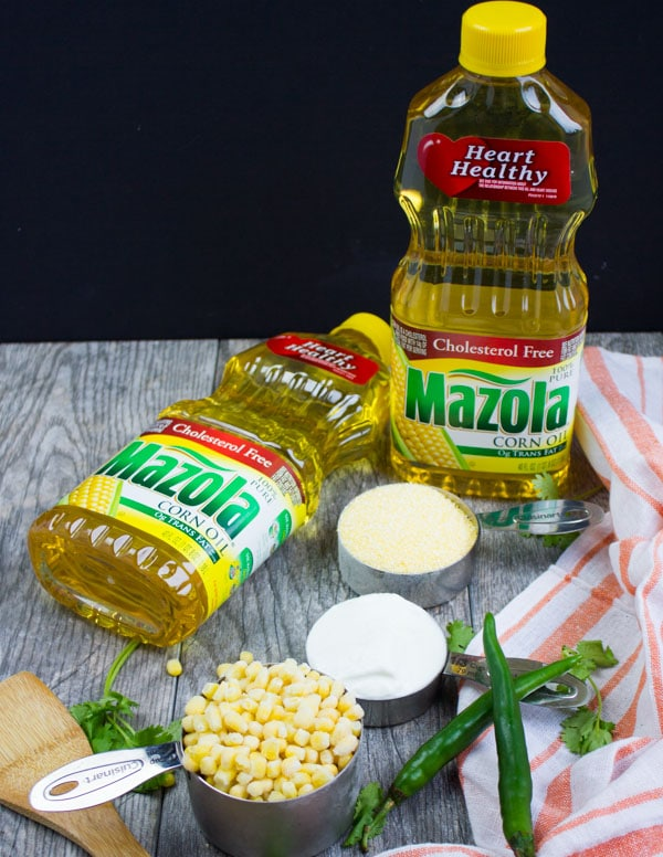 A set of ingredients including measured flour, cornmeal, fresh corn kernels, mazola oil bottles, green chillies