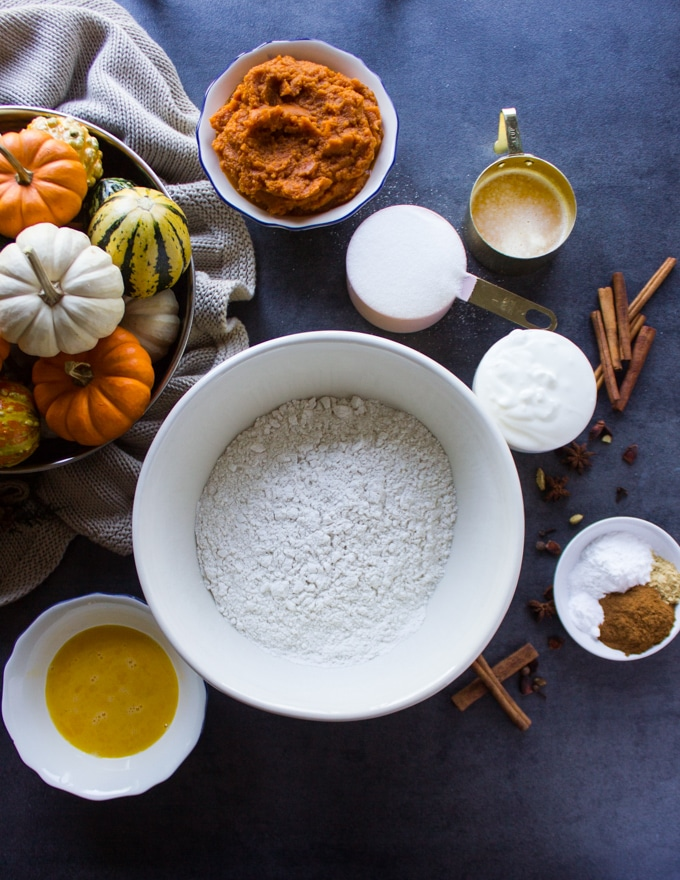 Ingredients for the pumpkin donuts a flour bowl, a spice bowl, melted butter, eggs, spice, sugar, yogurt and pumpkin puree