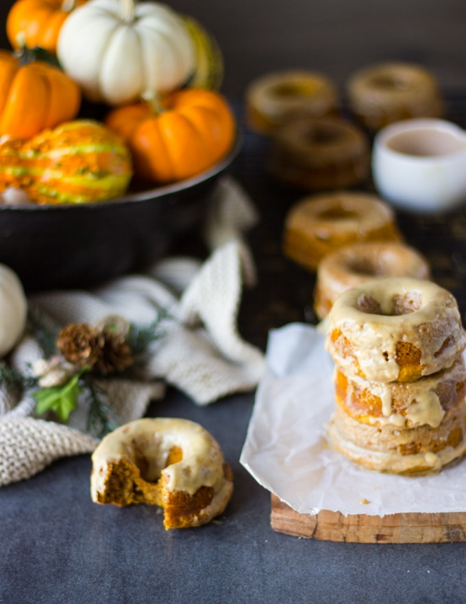 A bitten baked pumpkin donut on a surface with extra stacked pumpkin donuts in the background