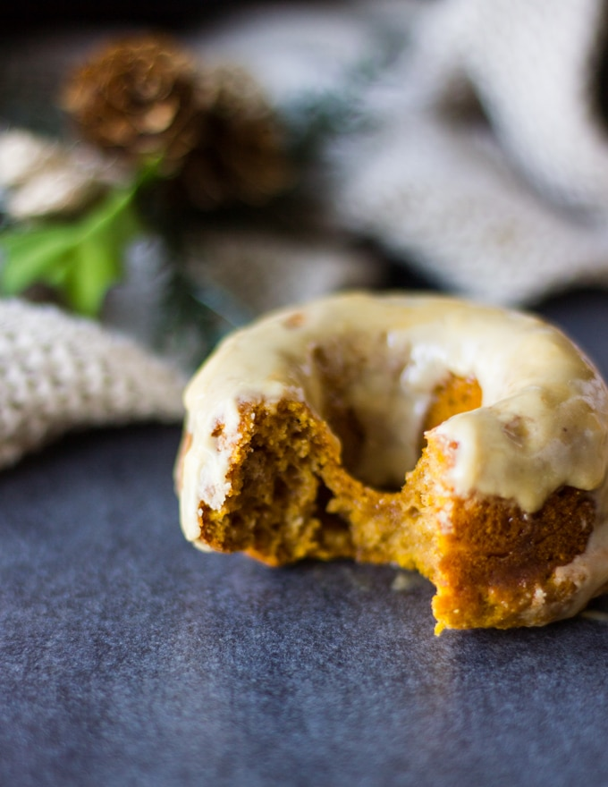 Close up of a bitten pumpkin donut showing the fluffy texture inside