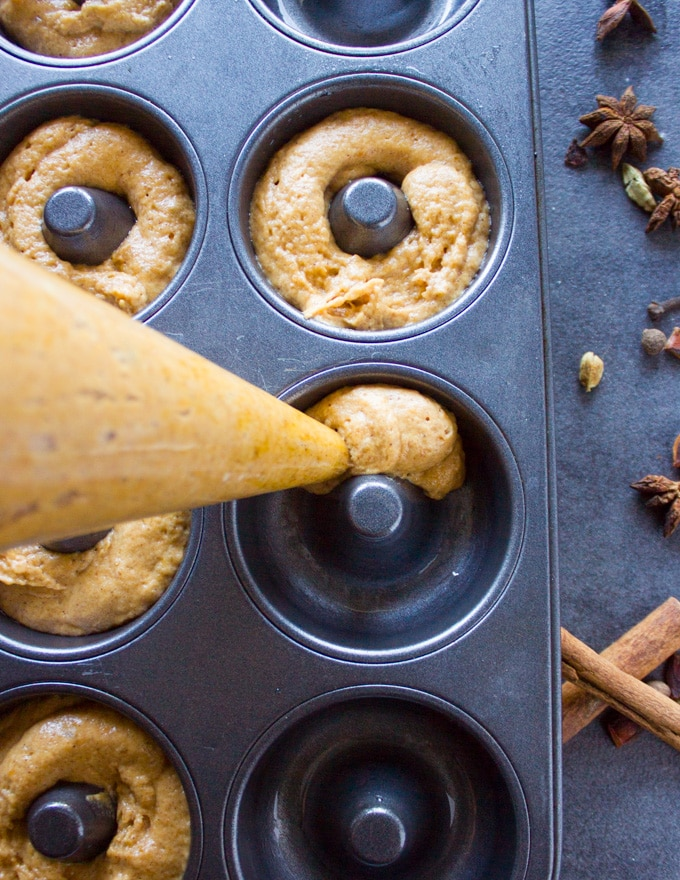 A bag piping the pumpkin donut batter into a donut pan