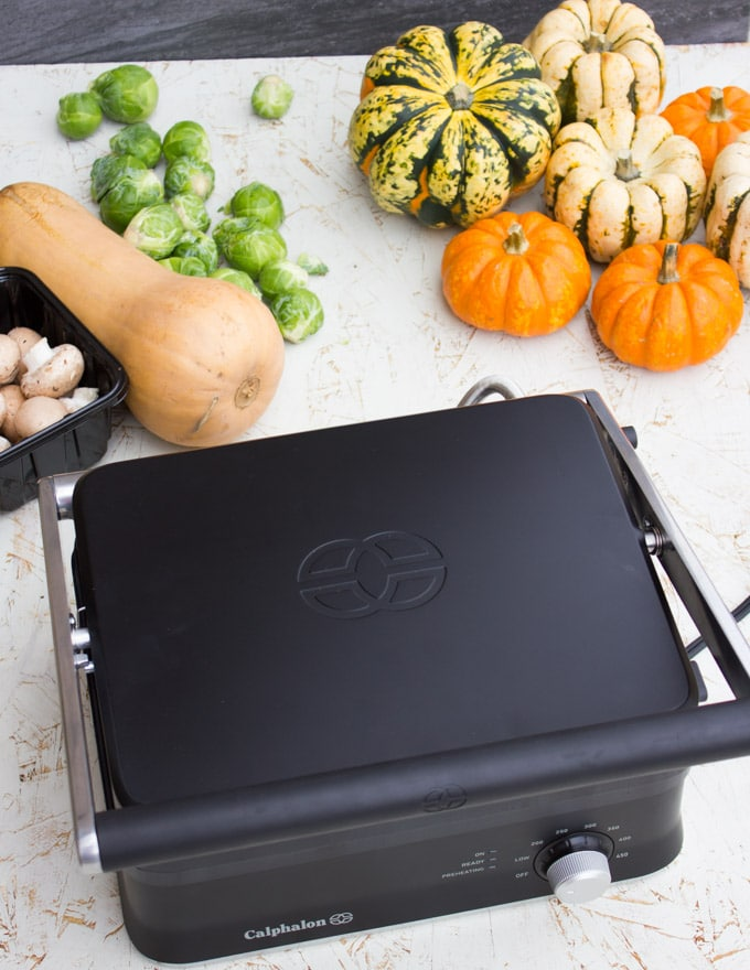 The Calphalon indoor grill surrounded vy the veggies to be grilled and pumpkins