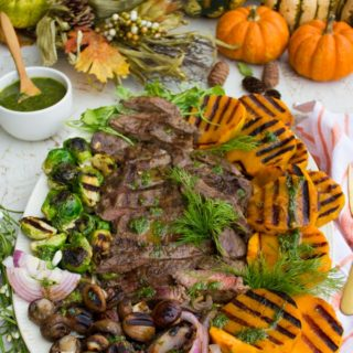 A platter showing grilled steak, grilled fal veggies and a bowl of dill dressing, some pumpkins on the side.