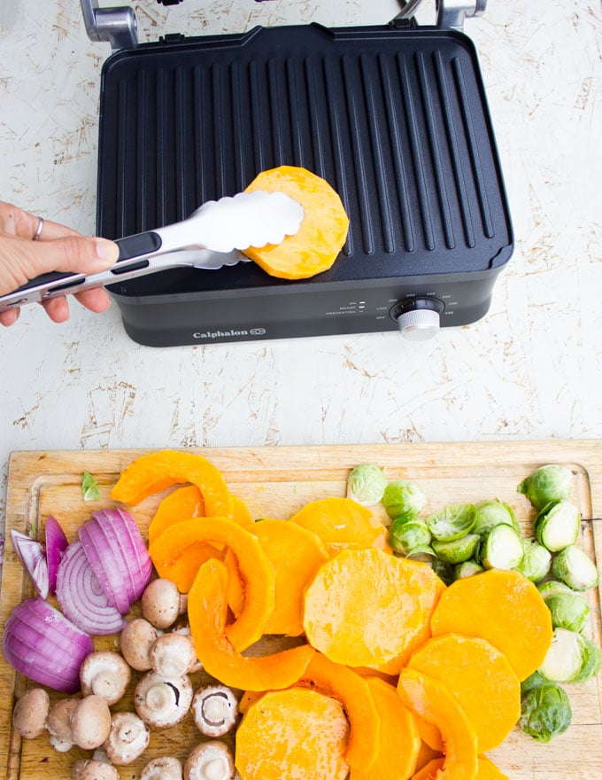 A hand placing the squash slices on the grill