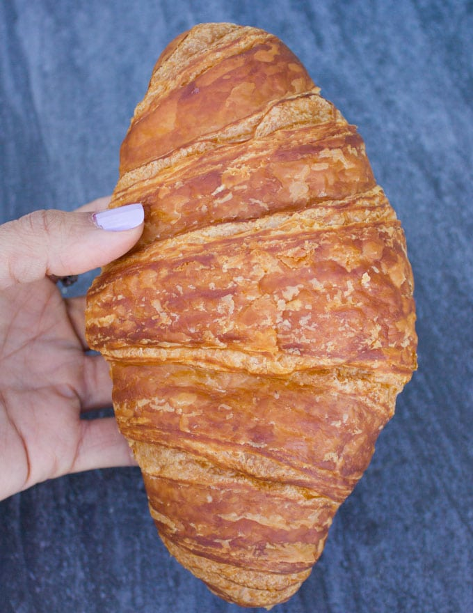A hand holding a whole croissant