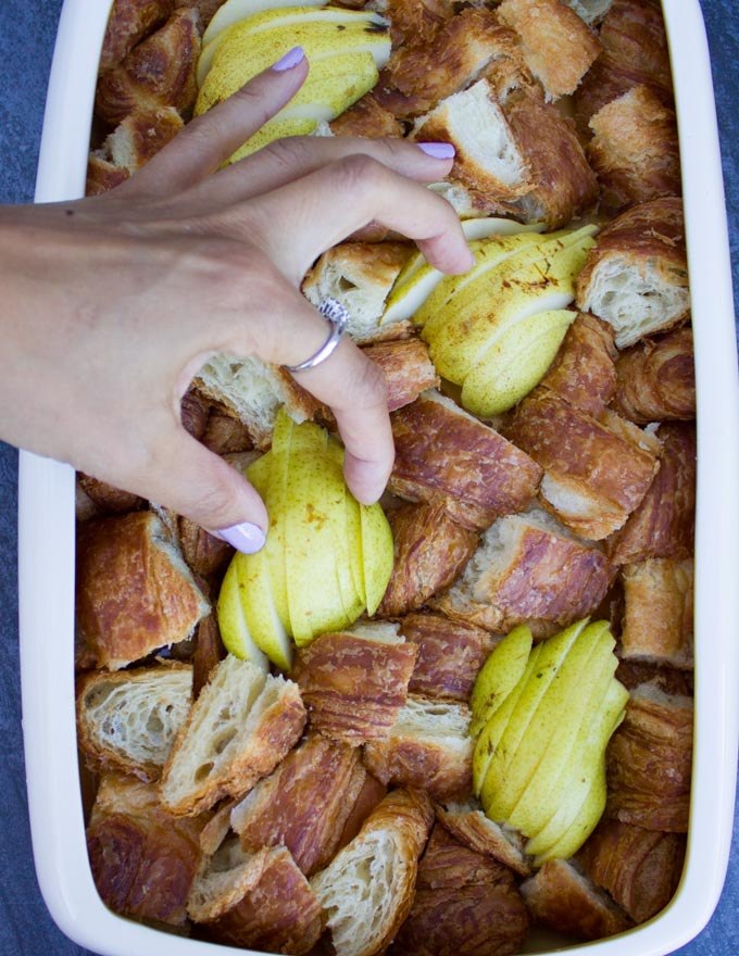 a hand placing some sliced pears in between the croissant cubes