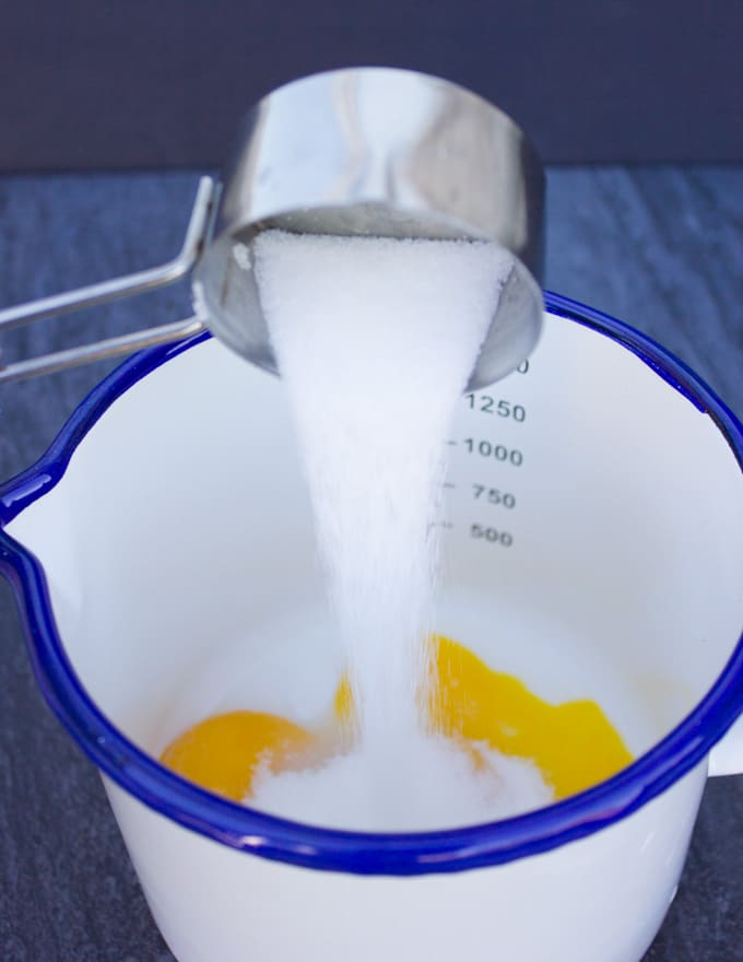 sugar poured over the egg yolks in a small pot